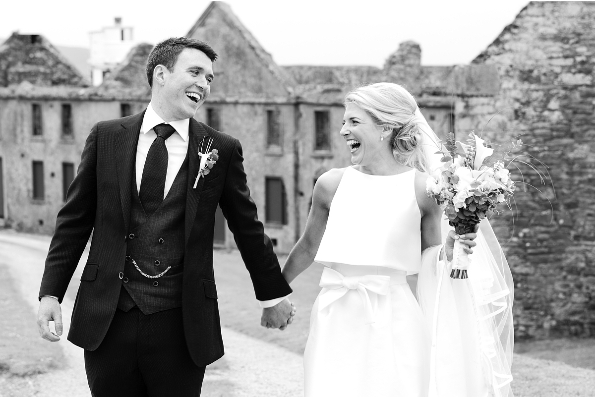 black and white photo of bride and groom holding hands and laughing at eachother