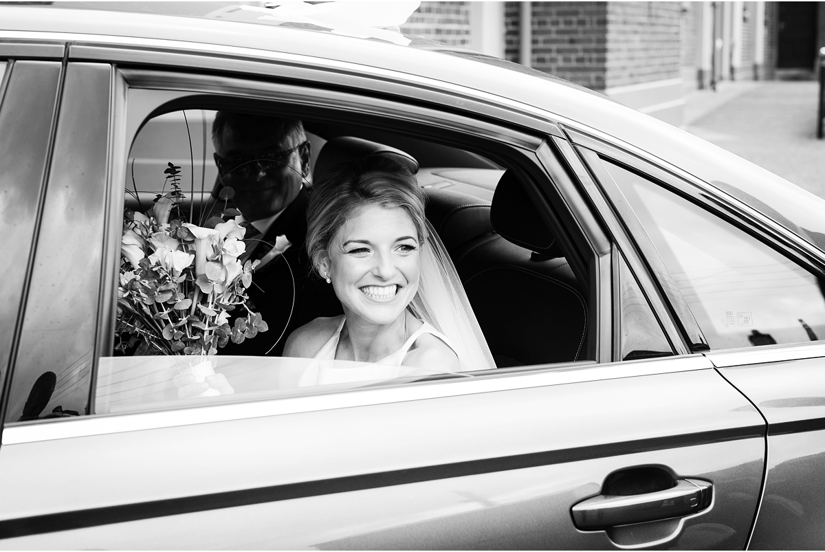 black and white photograph of bride beeming looking out of car window on arrival at chuch