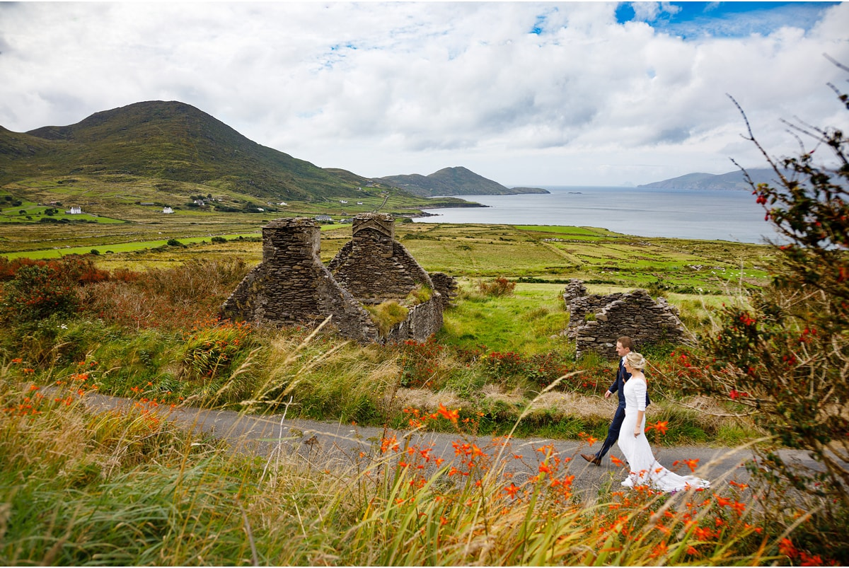 Bride and groom walk through an idilic Kerry landscape, with old tumbled cottages, green fields, mountains and the sea