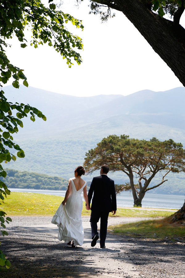 bright sunshiny photograph of a bride and groom walking away at Killarney golf course taken by female wedding photographer claire o'rorke