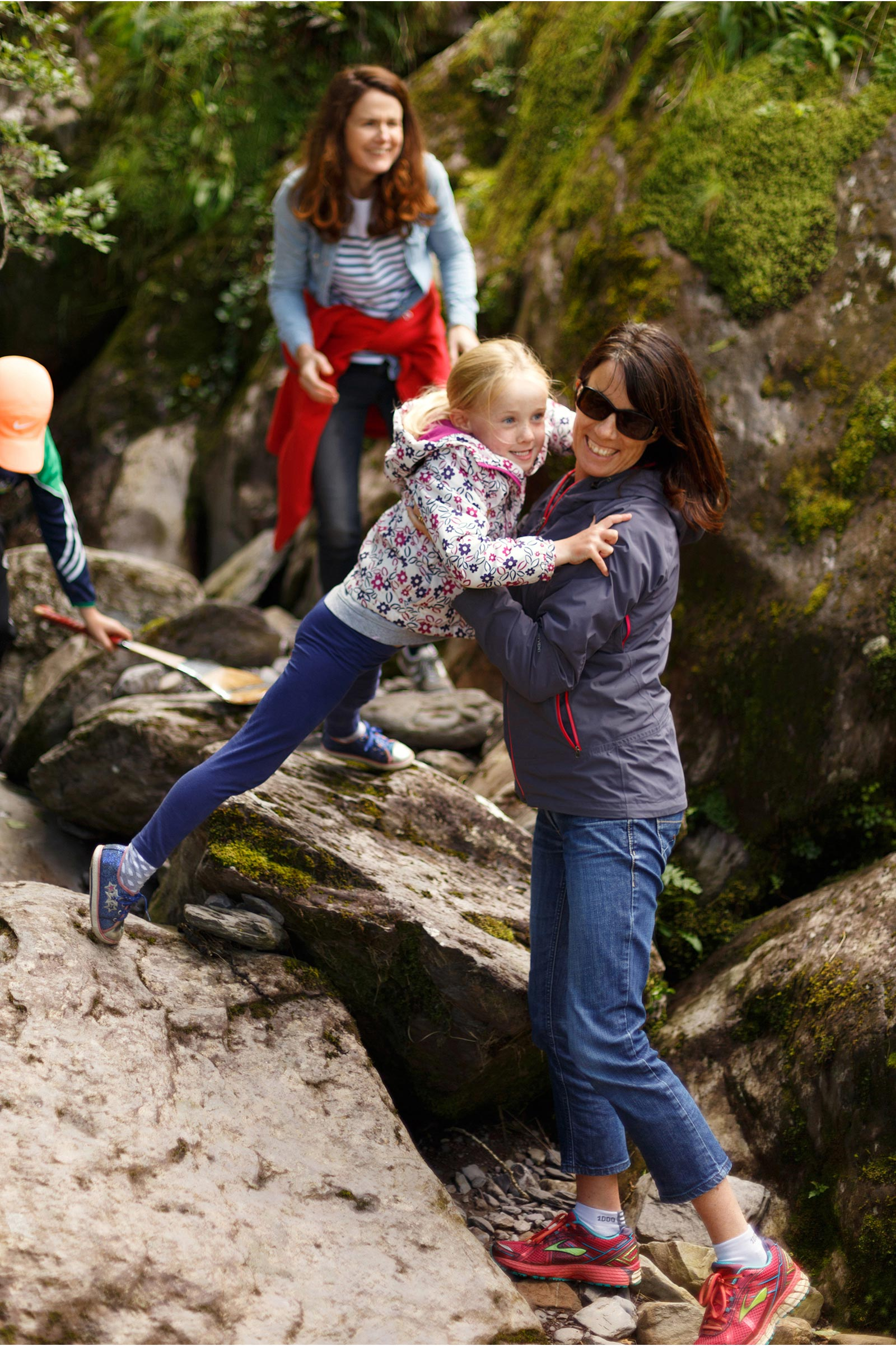 Mum helps small daughter across the rocks in a river in Gougane Barra