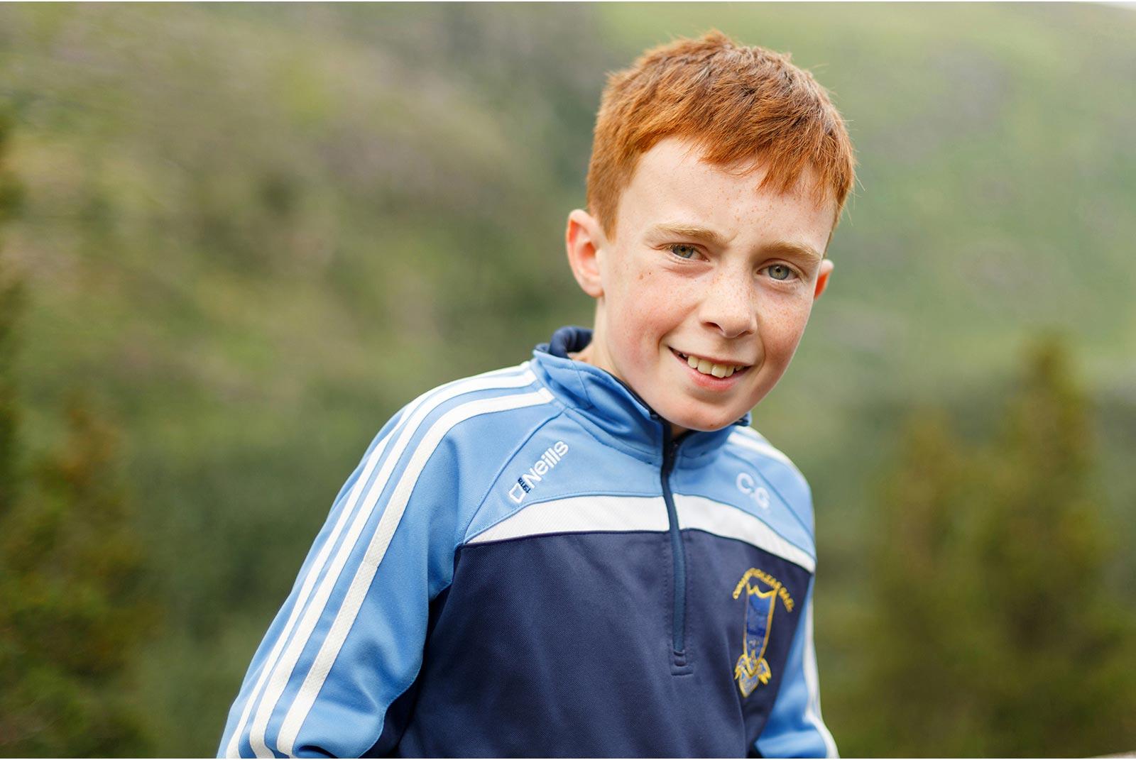 Smiling Irish boy looks beautiful set agains the green hills