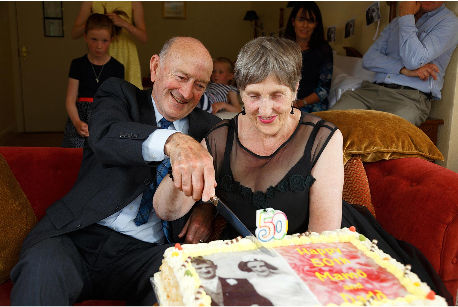 Couple cut into a big cake celebrating their 50th wedding anniversary