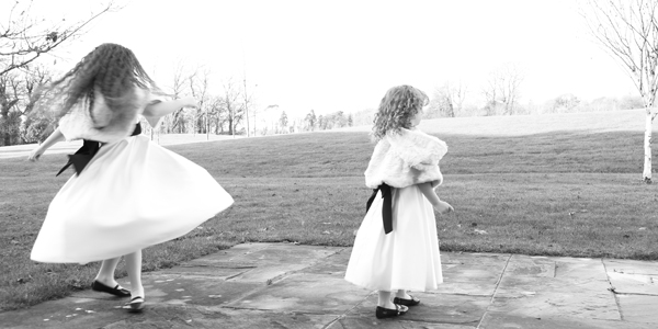 black and white image of two flower girls twirling