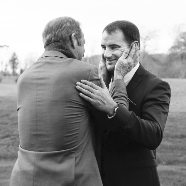 black and white photograph of proud dad holding his sons face on the day of his wedding
