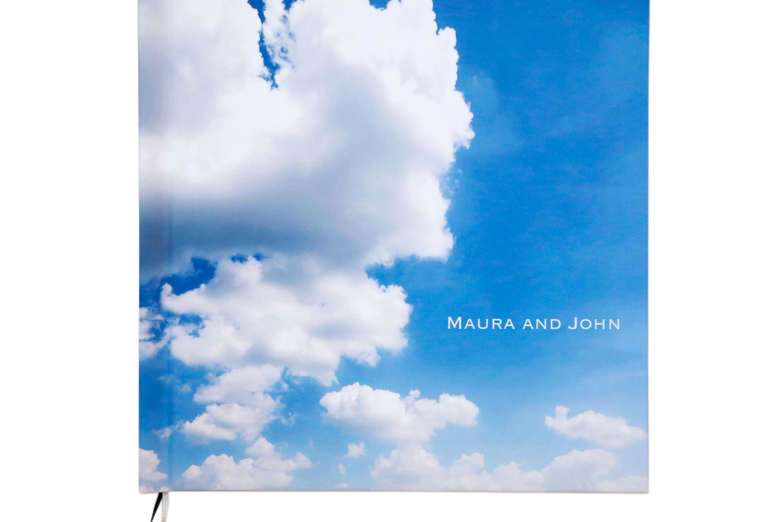 Wedding album cover with photograph of blue sky and white clouds